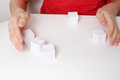 Children hands play with five small paper cubes on white table Royalty Free Stock Images