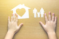 Children hands with small model of house and family Royalty Free Stock Photo
