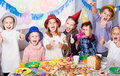 Children having celebration of friend's birthday during dinner Royalty Free Stock Photo