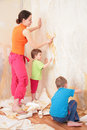 Children help mother remove  from wall old wallpap Stock Photos