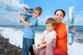Children help mother to glue beach sea wall-papers Royalty Free Stock Photo