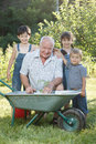Children is helping her grandfather in the garden teaches to plant plants Stock Image