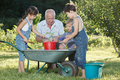 Children is helping her grandfather in the garden teaches to plant plants Royalty Free Stock Photography