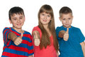 Children hold their thumbs up three smiling on the white background Royalty Free Stock Image