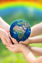 Children holding earth in hands against green spring background elements of this image furnished by nasa Royalty Free Stock Image