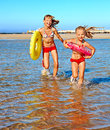 Children holding hands running on beach happy with ball Stock Photography