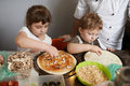 Children impose ingredients for pizza the Royalty Free Stock Photos
