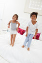 Children jumping on bed in pajamas together smiling to camera Stock Photos