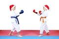 Children in karategi and in caps of santa claus are the standing in rack of karat Stock Image