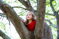 Children kid girl playing climbing to a tree in a park outdoor Royalty Free Stock Photo