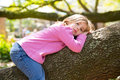 Children kid girl resting lying on a tree branch Royalty Free Stock Photo