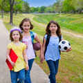 Children kid girls walking to schoool with sport balls folders and backpacks in outdoor park Royalty Free Stock Photo
