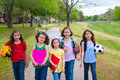 Children kid girls walking to schoool with sport balls folders and backpacks in outdoor park Royalty Free Stock Image