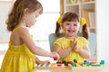Children kids play with educational toys, arranging and sorting colors and shapes. Learning via experience conception.