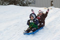 Children kids sledding toboggan sled snow winter two a boy and a girl down a hill together on a in the in the Royalty Free Stock Photo