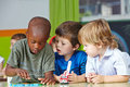 Children in kindergarten playing three with building blocks and cars Royalty Free Stock Images