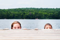 Children in a lake two peeking over dock Royalty Free Stock Photography