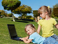 Children with laptop on green grass. Royalty Free Stock Photo