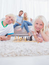Children lying on carpet playing chess in the living room Royalty Free Stock Photos