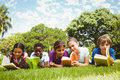 Children lying on grass and reading books Royalty Free Stock Photo