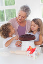 Children making cake with granny Stock Photo
