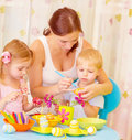 Children with mother paint eggs two small cute beautiful easter at home mom teaching babies decorate traditional eastertime symbol Stock Photography