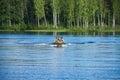 Children in motor boat swim on lake
