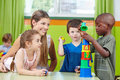 Children with nursery teacher building tower in a kindergarten group Royalty Free Stock Image