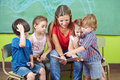 Children and nursery teacher reading book together in kindergarten Royalty Free Stock Photo