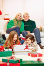 Children opening gifts at christmas two surprised with grandparents Stock Image