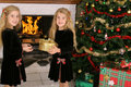 Children opening presents by fireplace Stock Photo