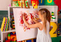 Children painting finger on easel in art class. Royalty Free Stock Photo