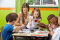 Children painting with nursery many together teacher in a kindergarten Royalty Free Stock Photography