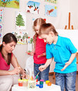 Children painting with teacher. Royalty Free Stock Images