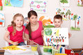 Children painting with teacher in art class. Royalty Free Stock Photo