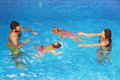 Children with parents swimming underwater in blue pool Royalty Free Stock Photo
