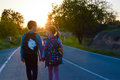 Children and pets on the roa walking road together holding hands at sunset they have their with them Royalty Free Stock Photo
