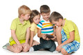 Children plaing with a new gadget group of four little are playing Stock Photography