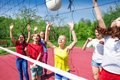 Children play actively near the volleyball net on court during sunny summer day outside Royalty Free Stock Images