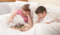Children play chess in a bed Royalty Free Stock Image