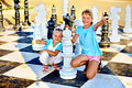 Children play chess outdoor. Royalty Free Stock Photo