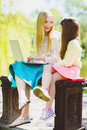 Children play laptop. Girls sitting against trees and lake outdoor Royalty Free Stock Photo