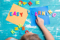 Children play plastic letters to combinations word `Easy Learning`