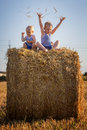 Children play sitting on a haystack small Royalty Free Stock Photography