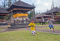 Children play soccer near the temple ulun danau in bali dynamic image of young boys who football main water on bratan lake Royalty Free Stock Photo