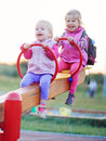 Children play teeter-totter outdoor Royalty Free Stock Photo
