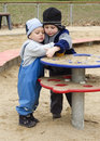 Children at playground playing with sand in a on a cold day Royalty Free Stock Photo