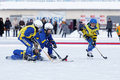 Children playing bandy on an outdoor stadium.