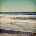 Children playing at beach silhouettes of two ocean vintage colors with vignette Stock Images