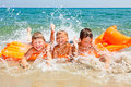 Children playing on a beach three kids splashing water Stock Image